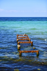 The rust-eaten piles of the old pier protrude from the seabed. Metal base of the former fishing pier, resting place for seagulls. Mediterranean coast. Selective focus.