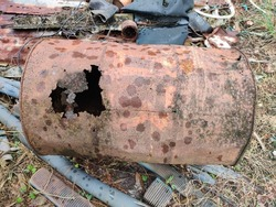 The rusted steel tank rotted into holes. Cannot be used to be placed on the ground with piles of useless items. being placed outdoors There are traces of rain falling on the surface of the old tank.