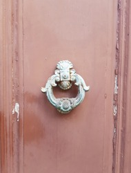 The rusty metal knocker on the dilapidated wooden door.