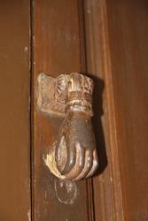 The rusty metal knocker on the old dilapidated wooden door, Cordoba.