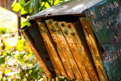 The rusty old mailboxes on the autumn nature. Abandoned iron mailboxes with house numbers.