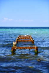 The rusty structure of the old pier sticks out of the seabed. Metal base of the former fishing pier, resting place for seagulls. Mediterranean coast. Selective focus.