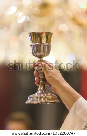 The sacred gesture during the christian mass: showing the holy goblet with Jesus Blood #1052288747