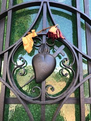 The sacred heart of Jesus with a dieing flower - dead rose above iron sculpture of a heart pierced by a knife with a cross on top. Detail of a cemetery door - iron gate with religious symbol. Devotion