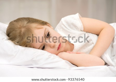 The sad little girl lying in bed