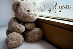 The sad teddy bear sits on the windowsill and looks sadly out the window, it's raining, the glass is covered with drops. Handwritten inscription on a glass