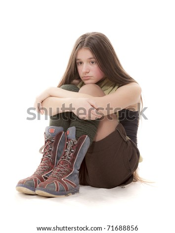 The sad teenager sits on a white background