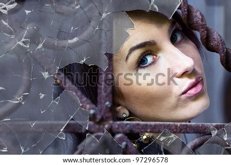 The sad woman behind a broken window.
