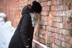 The sad young girl leaned her head against the brick wall