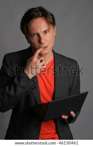 The sad young man holds a finger in a mouth and the laptop in a hand