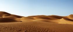The Sahara desert with sand dunes and blue sky