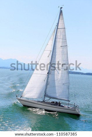 The sail boat in early morning on the mountain lake. Chiemsee is a biggest freshwater lake in Bavaria, Germany.