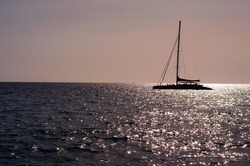 The sailboat (yacht) goes forward against the background of the horizon and the pink sunset