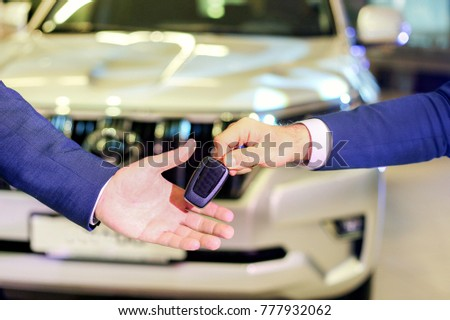 The sales manager hands over the keys to the new owner of the car. The concept of buying a car from the salon