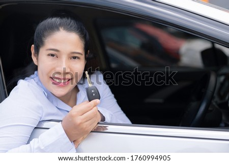The saleswoman holds the new car keys. Ready to deliver to customers at the showroom.