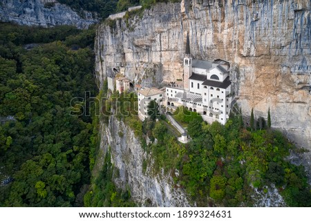 The sanctuary is high in the mountains of Italy. The unique Sanctuary Madonna della Corona church was built in the rock. Aerial view of the church on the sheer cliff. Italian church in the Alps. Stockfoto ©
