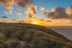 The sand dunes of Oostende (Ostend in English) and Bredene at sunset with the skyline and pier of Ostend in the background, West Flanders, Belgium.