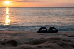 the sandal on the beach with the sunset background the holiday conceptual image