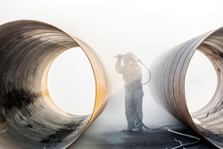 The sandblaster is sandblasting to the pipe materials. A sandblasting system includes four basic components: the air source, the sandblasting cabinet, the dust collector, and the blasting media.