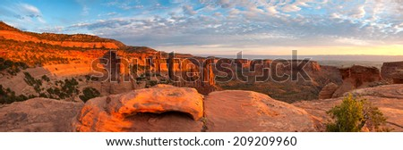 The sandstone red rock of Colorado National Monument glows under a sunrise.
