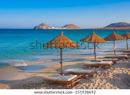 The sandy beach near the blue sea with sun beds and umbrellas. Mykonos