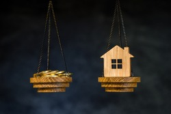 The scales with the coins and the home of the imitation of bamboo. The concept of purchasing housing, credit, and quotes on the real estate market.