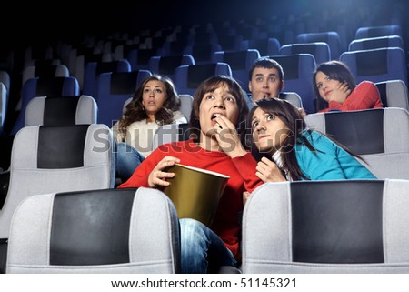 The scared young people at cinema viewing