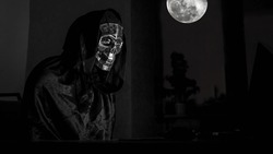 The scary reaper looks into a laptop monitor, a character of Halloween. Human skull. Skull character and moon.
