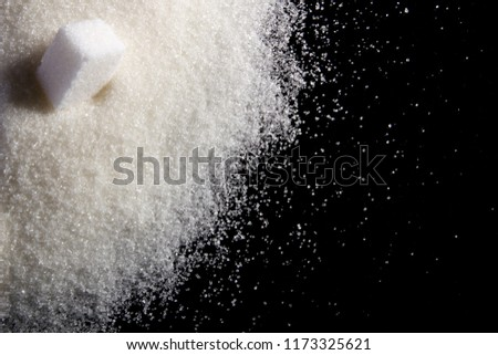 The scattered sugar. On granulated sugar the sugar cube lies. Top view.