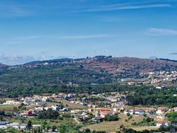 The scenery near Fatima city in Portugal consists of  houses and building in the foreground and the wind farm in the background.