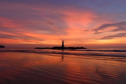The scenery of the silhouette of Khao Lak lighthouse in sunset time with the dramatic twilight sky at Phang-Nga, Thailand.