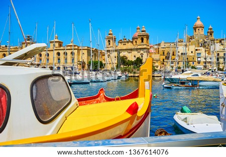 The scenic cityscape of historical city of Birgu with Vittoiosa marina and vintage boat's bow on the foreground, Malta.