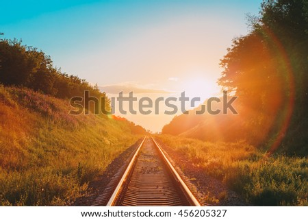 The Scenic Landscape With Railway Going Straight Ahead Through Summer Hilly Meadow To Sunset Or Sunrise In Sunlight. Lense Flare Effect. #456205327