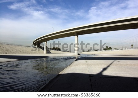 The scenic Los Angeles as it flow under a freeway overpass.