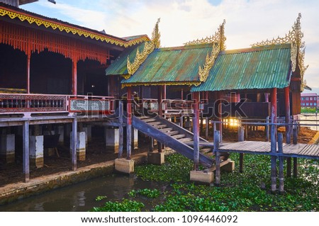The scenic stilt porch of Nga Phe Chaung monastery with carved golden decors on multi-level roof (pagoda), Ywama, Inle Lake, Myanmar. #1096446092