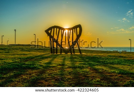 The scenic sunset in city park, the sun is seen through the stone heart on coast, Tel Aviv, Israel. #422324605
