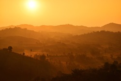 The scenic view of sunrise behind the mountain ranges giving the beautiful shades of orange in the sky and silhouette version of hills and trees, taking at rural area in Thailand. Pure nature.