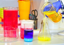 The scientist conducts demonstration experiments with solutions of various substances with the addition of dry ice, dye. The phenomenon of fluorescence.