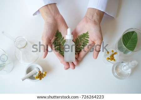 the scientist,dermatologist testing the organic natural  cosmetic product in the laboratory.research and development beauty skincare concept.blank package,bottle,container .cream,serum.hand #726264223