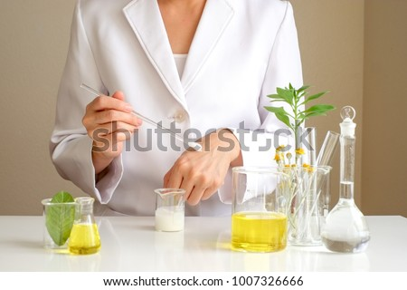 the scientist,dermatologist testing the organic natural cosmetic product in the laboratory.research and development beauty skincare .cream,serum.hand #1007326666