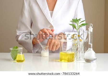 the scientist,dermatologist testing the organic natural cosmetic product in the laboratory.research and development beauty skincare concept.blank package,bottle,container .cream,serum.hand