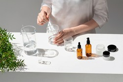 The scientist, dermatologist testing the organic natural cosmetic product in the laboratory. Vials, glass laboratory flasks. Beauty cosmetic research and development concept.