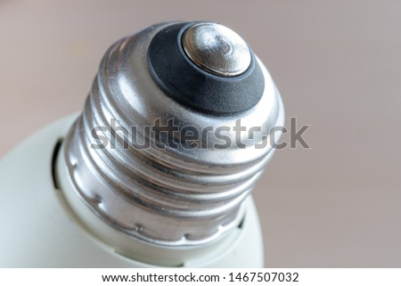 The screw threads part of a compact fluorescent light bulb. Close up image