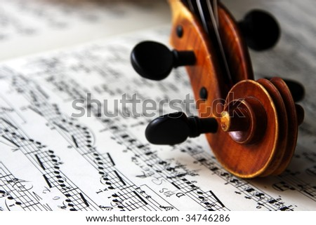 The scroll of an old Italian violin on sheet music.