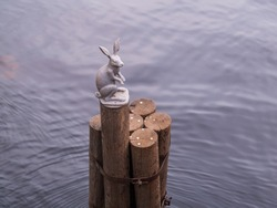 The sculptural figure of a hare on wooden stilts as a symbol of the Peter and Paul Fortress near the bridge in the city of St. Petersburg