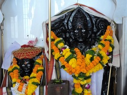 the sculpture holy sacred hindu god lord kalbhairav and lord khandoba the avtar of lord shiva. black stone sculpture statutes of gods with decorated flowers neckless and clothes and jewelery