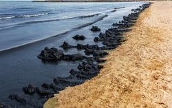 The sea and the beach are polluted with oil. A crude oil spill on the sand of a city beach. Beach oil spill impact, pollution, waste disposal. Ecological catastrophy. Selective focus