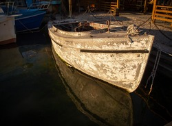 The sea boat is old and rusty, standing on the dock. Concept of water safety, recycling of old vehicles.