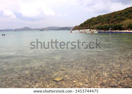 The sea sees the mountains and has clear water to see the rocks.