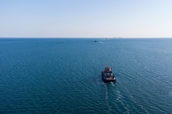 The sea tug moves from the port water area towards the open sea. Photo from the helicopter. View from above